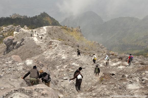 beberapa pendaki menuruni terjalnya jalur gunung merapi
